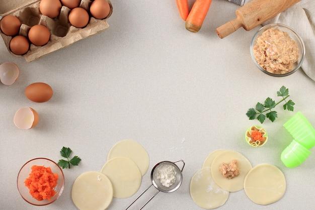 Composition à plat avec boulettes crues (dim sum) et ingrédients sur fond gris. copiez l'espace pour le texte, processus de cuisson