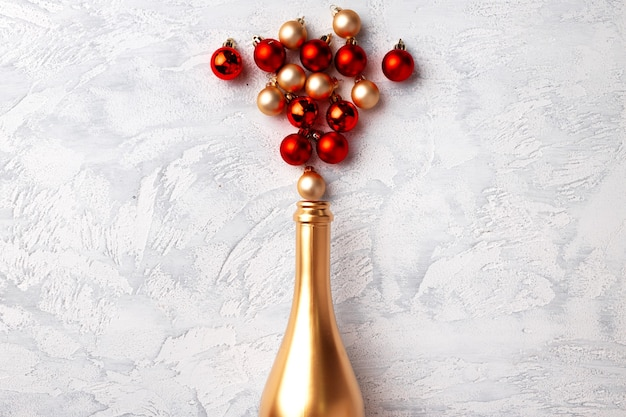 Composition à plat avec bouteille de champagne or et boules de noël
