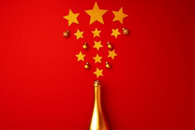 Composition à plat avec bouteille de champagne or et vue de dessus de boules de noël