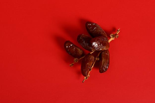 Composition à plat avec une branche de dattes sucrées fraîches et savoureuses pour le petit-déjeuner après interruption et jeûne du ramadan
