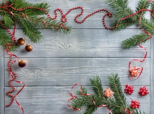 Composition à plat avec des branches de sapin, serpentine, boules de sapin, sur un fond en bois.