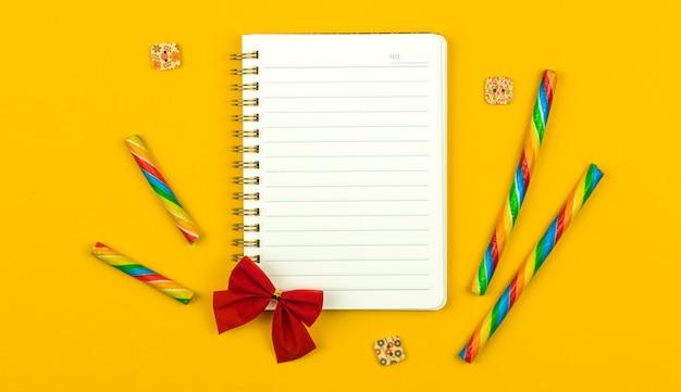 Composition à plat avec cahier vierge, fond jaune vif avec concept d'accessoires de mode