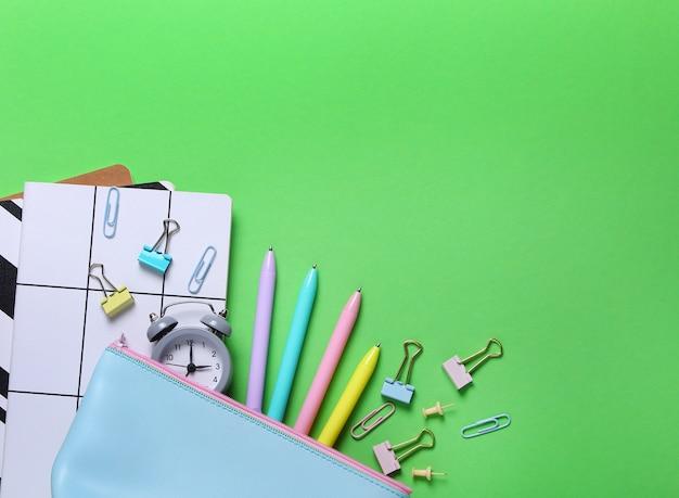 Composition à plat de cahiers, crayon, stylo, reliure, réveil sur vert.