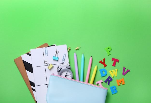 Composition à plat de cahiers, crayons, stylos, cartables, réveil, lettres de couleur sur vert.