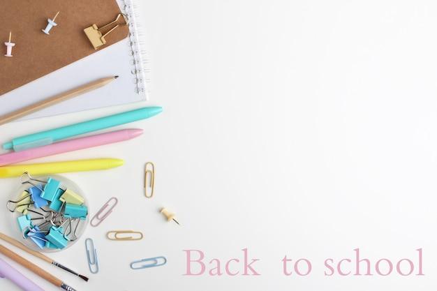 Composition à plat de cahiers, stylos, crayons, reliures, notes autocollantes, trombones et pinceaux.