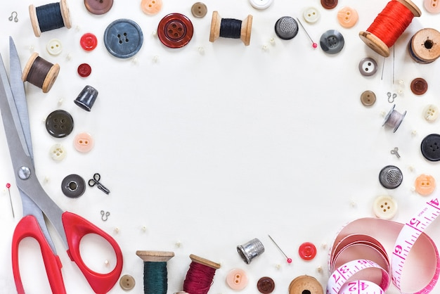 Composition à plat avec des ciseaux et des fournitures de couture sur fond blanc