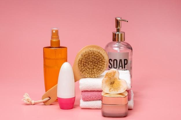 Composition à plat avec des cosmétiques spa et une serviette sur fond rose