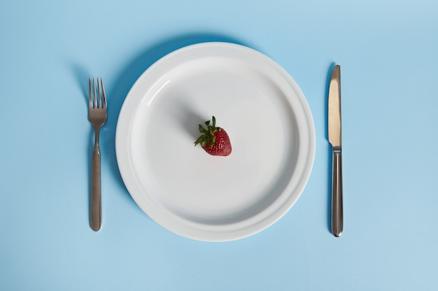 Composition à plat avec une délicieuse fraise sur une assiette, une fourchette et un couteau isolés. concept de saine alimentation.