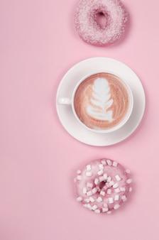 Composition à plat avec deux beignets et tasse de café sur rose