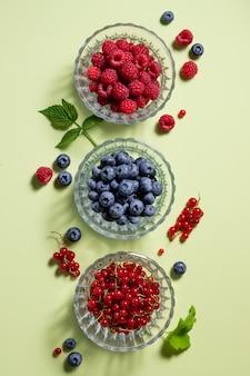 Composition à plat avec différentes baies dans des bols en verre sur fond vert alimentation saine