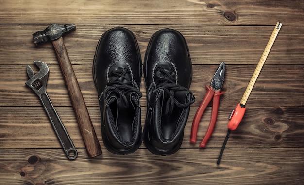 Composition à plat avec différents outils et instruments de travail industriels, équipements de sécurité sur fond en bois. vue de dessus
