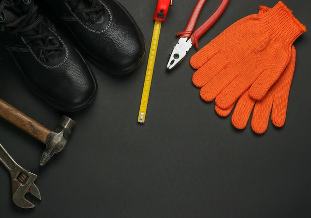 Composition à plat avec différents outils et instruments de travail industriels, équipements de sécurité sur fond jaune. copiez l'espace. vue de dessus