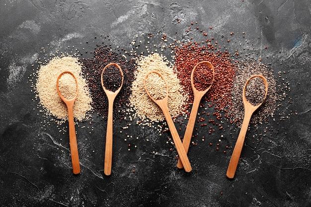 Composition à plat avec différents types de quinoa sur fond noir. vue de dessus.