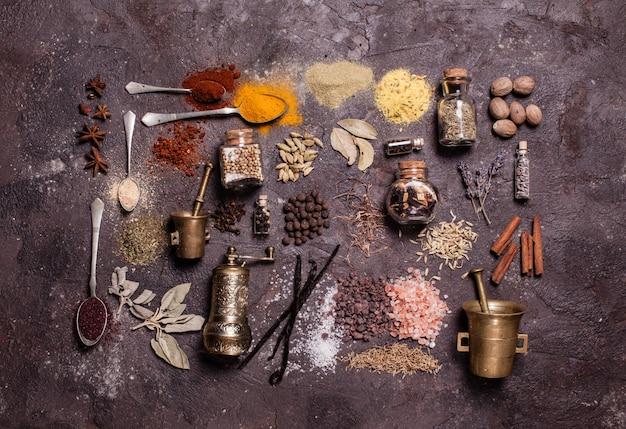 Composition à plat de diverses épices et mortiers sur fond d'ardoise brune, vue de dessus
