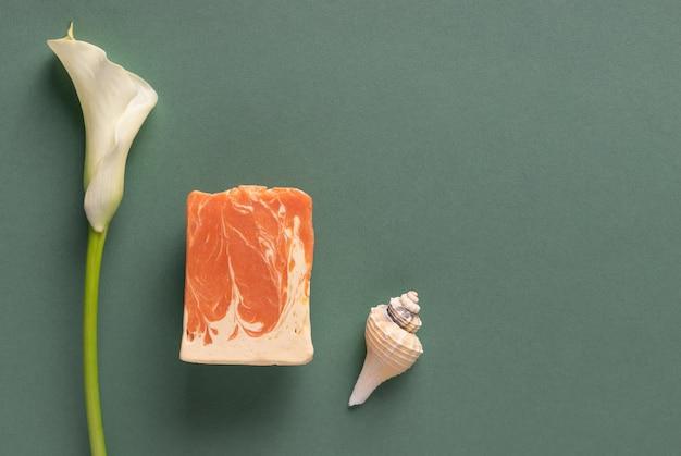 Composition à plat avec du savon à base de plantes naturelles sur fond vert. produits cosmétiques de bricolage. concept de soins corporels quotidiens. espace pour le texte
