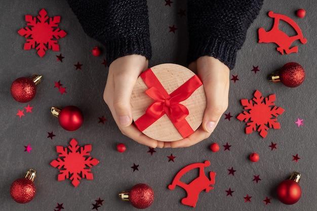 Composition à plat avec enfant tenant une boîte-cadeau et des décorations de noël rouges sur fond sombre