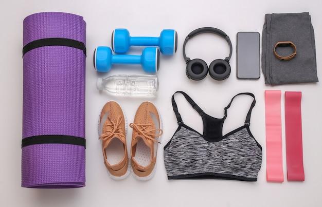 Composition à plat d'équipements sportifs, vêtements sur fond blanc. concept de remise en forme, de sport et de mode de vie sain. vue de dessus