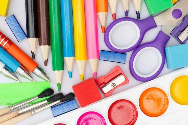 Composition à plat avec des fournitures scolaires sur fond de bois blanc peint des crayons en caoutchouc de brosse