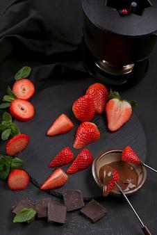 Composition à plat avec des fraises enrobées de chocolat sur fond gris