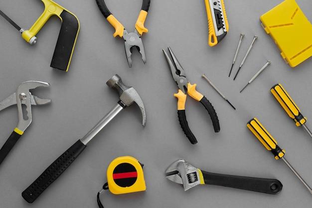 Composition à plat avec outils de construction et de réparation à domicile sur fond gris, espace pour le texte