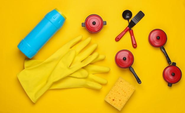 Composition à plat de produits de vaisselle, ustensiles de cuisine jouets et ustensiles sur fond jaune.