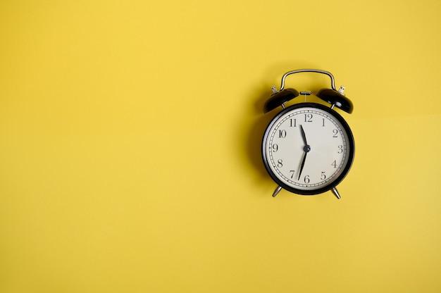 Composition à plat avec un réveil noir vintage sur fond jaune avec espace de copie pour ajouter du texte. concepts, entreprise, organisation, gestion du temps de la rentrée scolaire et de la journée des enseignants