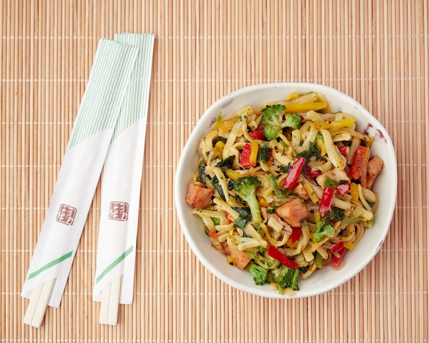 Composition à plat sur un tapis de bambou avec de la nourriture orientale dans un bol, des nouilles et des légumes et des baguettes