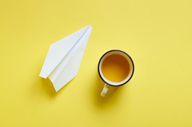 Composition à plat d'une tasse blanche de café ou de cappuccino et d'un avion en papier isolé. vue de dessus