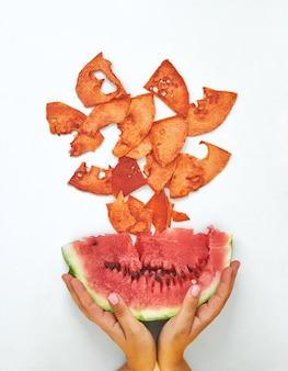 Composition à plat avec des tranches de pastèque fraîches et séchées sur fond blanc. snack bio végétalien cru naturel. concept de nourriture saine. vue de dessus.