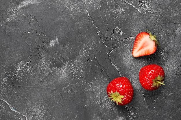 Composition à plat de trois fraises mûres sur fond sombre. vue de dessus