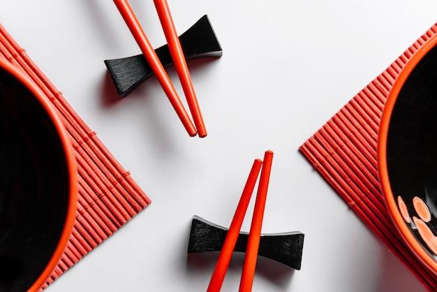 Composition plate avec des baguettes rouges, des serviettes et des tasses.