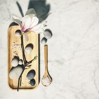 Composition plate avec de belles fleurs de magnolia de printemps et des pierres grises sur fond de marbre blanc. relaxation et zen comme concept.