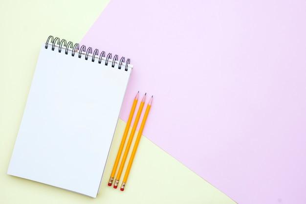 Composition plate avec un cahier vide avec des crayons sur fond rose et jaune