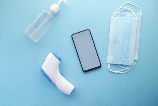 Composition plate du thermomètre de masque de téléphone intelligent et du désinfectant sur la table