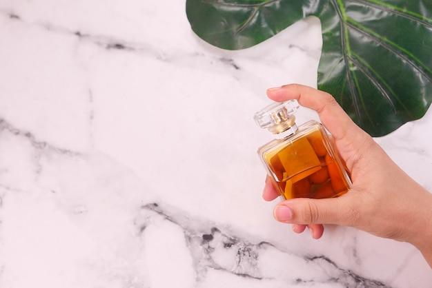 Composition plate de femmes main tenant le parfum sur fond de carreaux