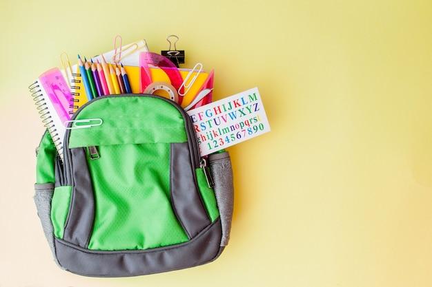 Composition plate laïque avec sac à dos et papeterie scolaire sur fond jaune.