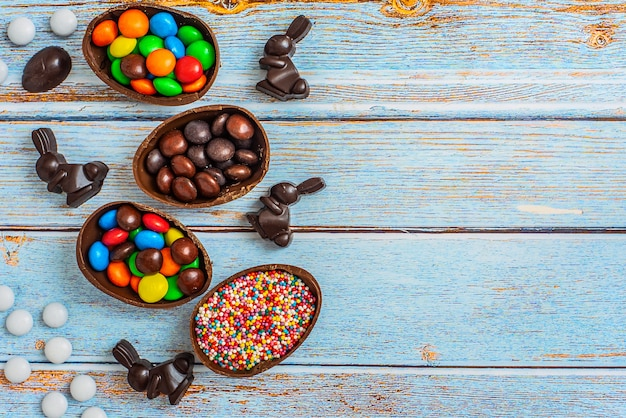 Composition plate avec des oeufs de pâques au chocolat, du lapin et des bonbons sur du bois bleu.