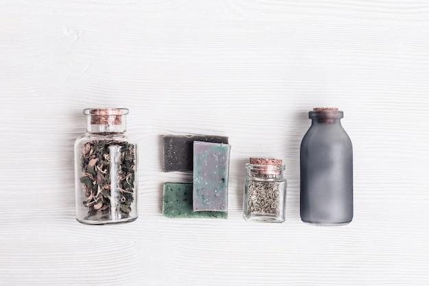 Composition plate avec de petites bouteilles en verre aux herbes parfumées et des barres de savon naturel avec des ingrédients de bricolage bio naturels. aromathérapie, fond de spa de beauté.