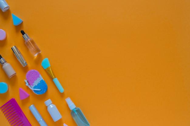 Composition plate avec des produits cosmétiques sur fond orange. éponges multicolores. soins personnels des femmes. image vue de dessus avec espace de copie.