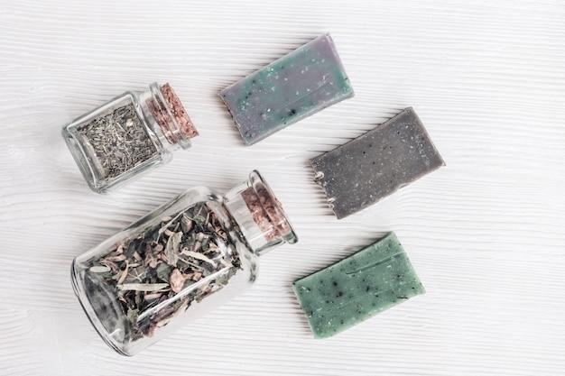 Composition plate avec produits cosmétiques pour salle de bain, savon naturel aux herbes parfumées naturelles. spa, aromathérapie et concept de traitement de soins corporels. vue de dessus avec espace copie.