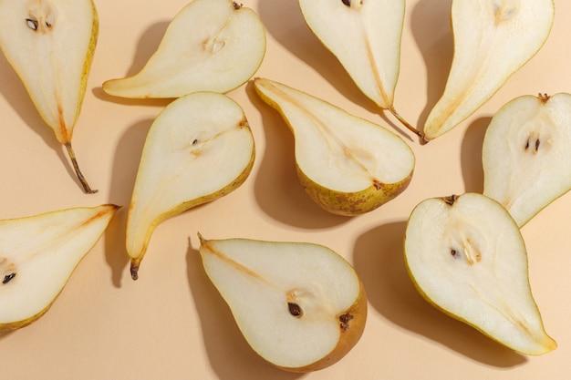 Composition de poires coupées sur un beige. vue de dessus.