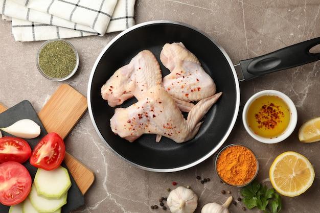 Composition avec poulet cru et épices sur fond gris. cuisson du poulet