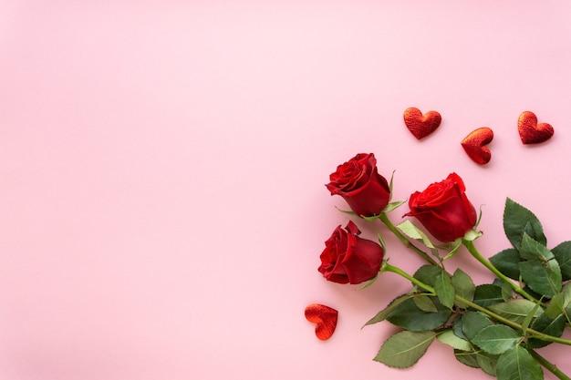 Composition pour la saint-valentin. bouquet de roses rouges et de coeurs sur fond rose, copyspace