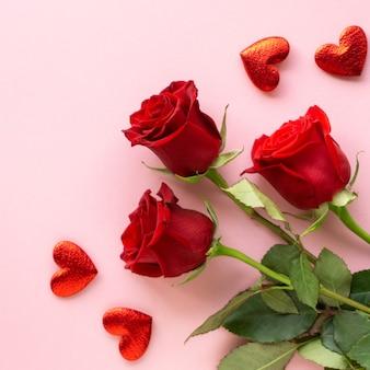 Composition pour la saint-valentin. bouquet de roses rouges et coeurs sur fond rose
