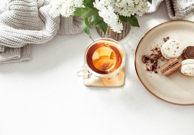 Composition printanière confortable avec une tasse de thé et de macarons français sur un tableau blanc.