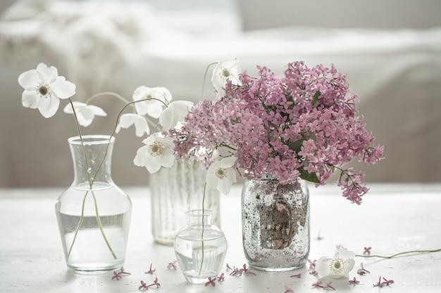 Composition printanière avec des fleurs dans des vases en verre à l'intérieur de la pièce.