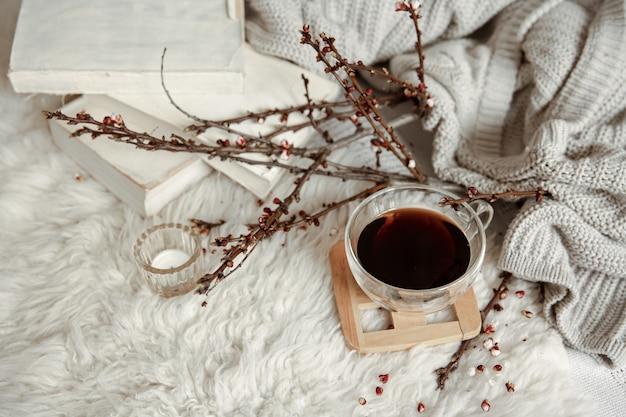 Composition printanière avec une tasse de thé, des branches fleuries et des détails de décoration.