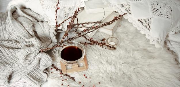 Composition printanière avec une tasse de thé, des branches fleuries et un élément tricoté.