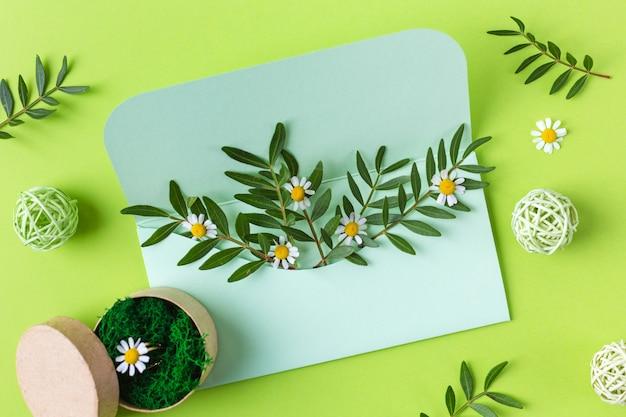 Composition de printemps avec une enveloppe et des fleurs vertes. 8 mars. vue de dessus