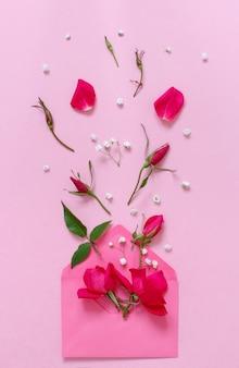 Composition de printemps avec enveloppe et roses roses sur fond rose vue de dessus